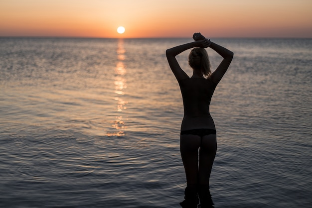Tourist in swimsuit watching the sunrise Free Photo