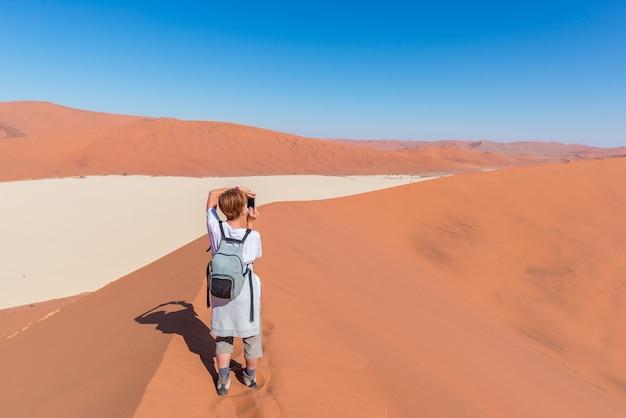 Tourist taking photo at sossusvlei, namibia Premium Photo