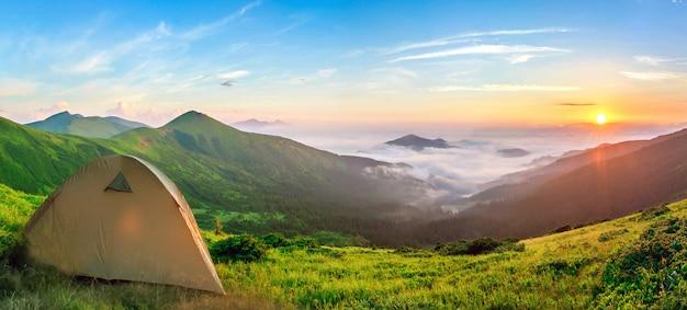 Туристическая палатка, расположенная в горах на закате Premium Фотографии
