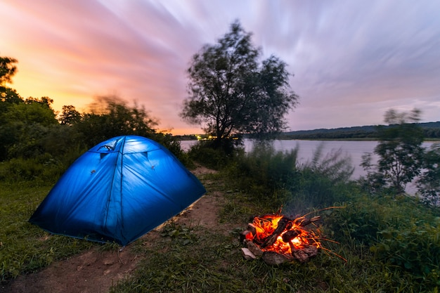 Tourist tent near the river. campfire burning low. early morning. beautiful sunrise sky. Premium Photo