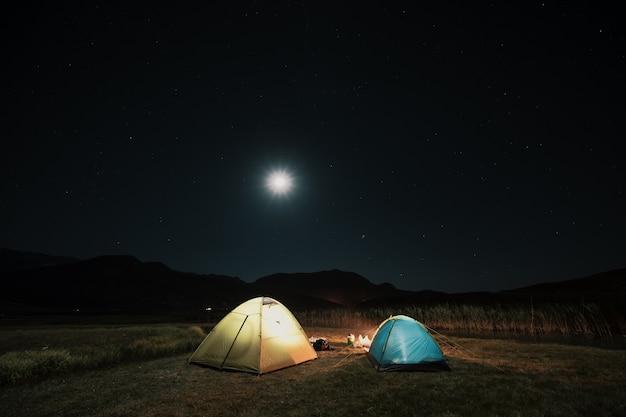 夜の山の牧草地の中でキャンプの観光テント 無料写真