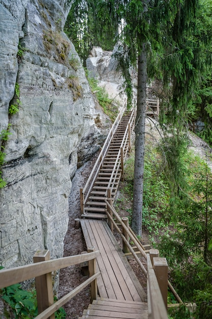 Tourist trail with wooden pathwalk and stairs near sandstone cliffs. the cliff of sietiniezis, latvia. gauja national park. Premium Photo