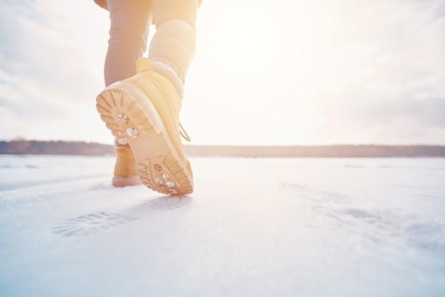 Tourist walking away through the snow in the sunset Premium Photo