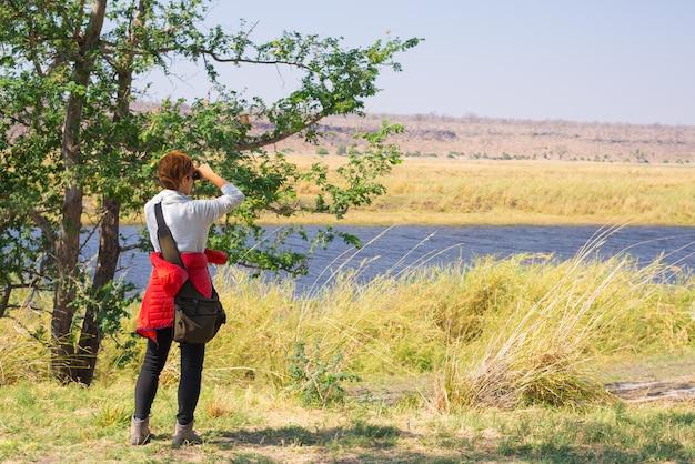 アフリカ、ナミビアボツワナ国境のチョベ川で双眼鏡で野生動物を見ている観光客。チョベ国立公園、有名なワイルドライフ保護区、高級旅行先。 Premium写真