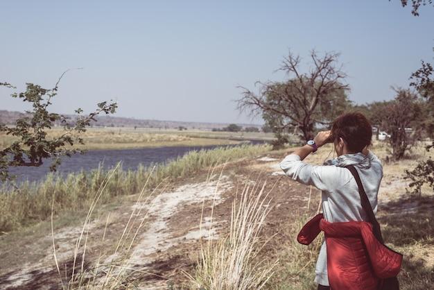 アフリカ、ナミビアボツワナ国境のチョベ川で双眼鏡で野生動物を見ている観光客。 Premium写真