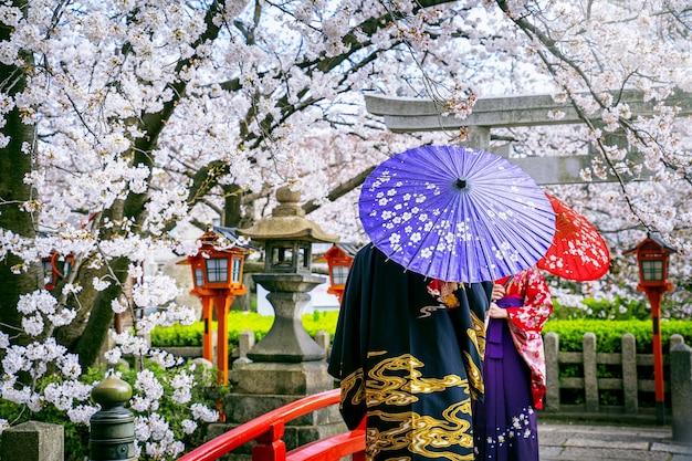 春に日本の伝統的な着物と桜を身に着けている観光客、日本の京都寺院。 無料写真
