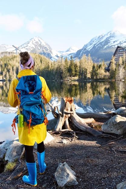 배낭을 든 관광객은 산 강 근처에 서서 아름다운 경치와 함께 야생의 자연을 즐기고 노란색 긴 아노락을 입습니다. 무료 사진