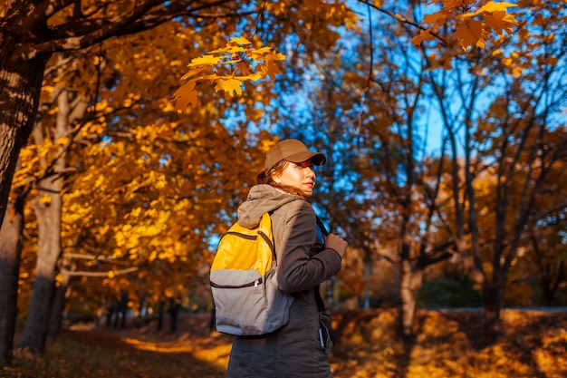 Tourist with backpack walking in autumn forest. young woman travel at sunset Premium Photo