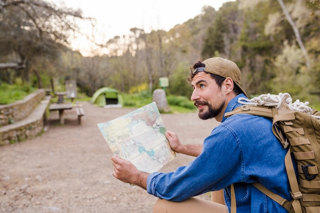 Tourist with map in nature Free Photo