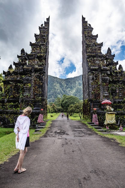 Tourist woman is looking to traditional balinese hindu gates Premium Photo