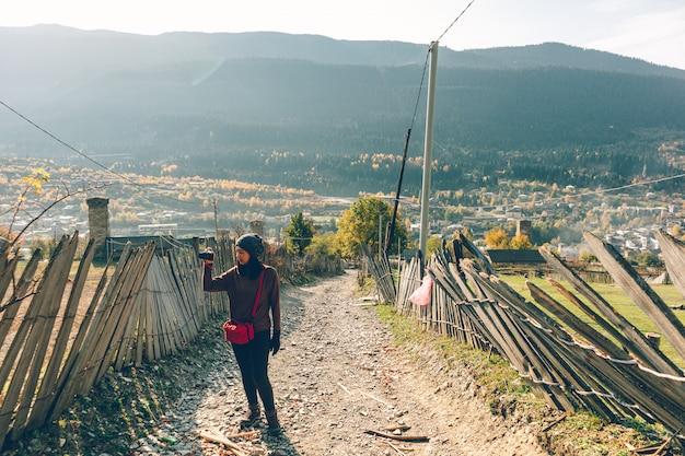 Туристическая женщина фотографирует на холме над маленьким сельским городком. Premium Фотографии