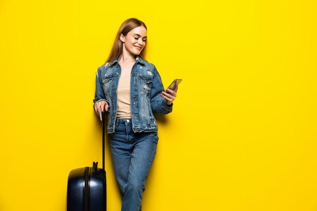 Туристическая женщина с чемоданом в летней повседневной одежды с телефоном, изолированные на желтой стене Бесплатные Фотографии