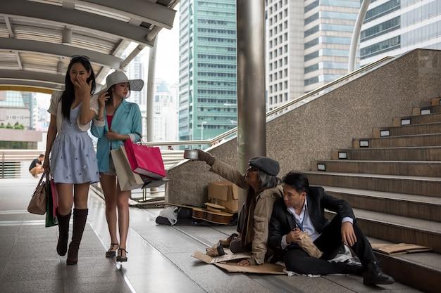 Tourist women look down the poor Premium Photo
