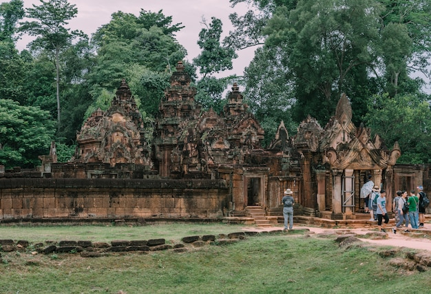Tourists admiring the east gopura of the second enclosure with the amazing carved pediment made of red sandstone in the banteay srei (citadel of the women) temple in cambodia. Premium Photo