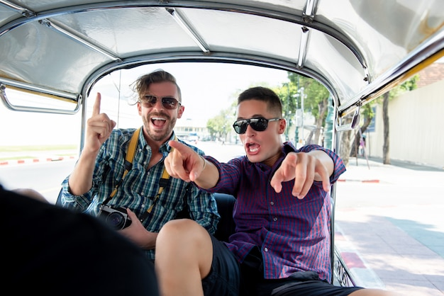 Tourists being excited and having fun on tuk tuk taxi in thailand Premium Photo