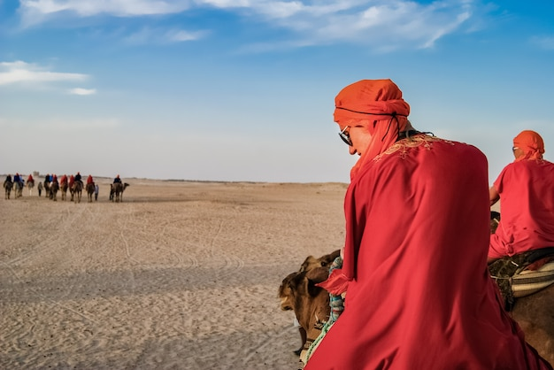 Tourists in the desert on camels. the entertainment of tourists. Premium Photo