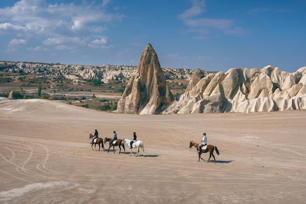 観光客はトルコのカッパドキアで乗馬を楽しんでいます 無料写真