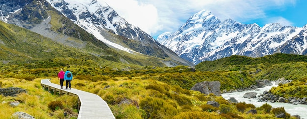 Tourists hiking on hooker valley track in mount cook national park, new zealand. Premium Photo