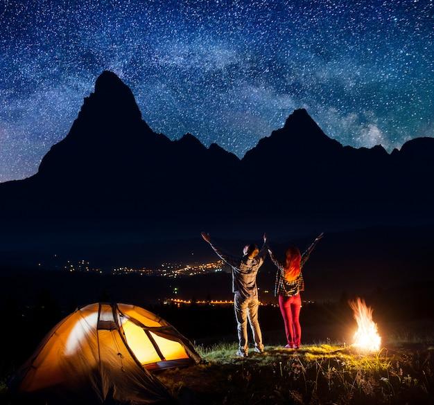 Туристы подняли руки под звездами возле костра и палатки Premium Фотографии