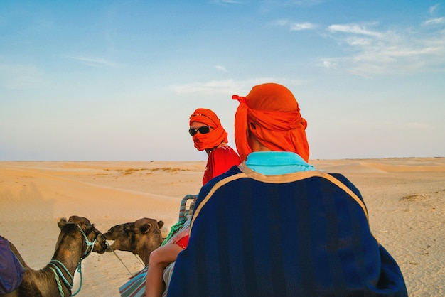 Tourists in the sahara desert on camels. the entertainment of tourists. Premium Photo