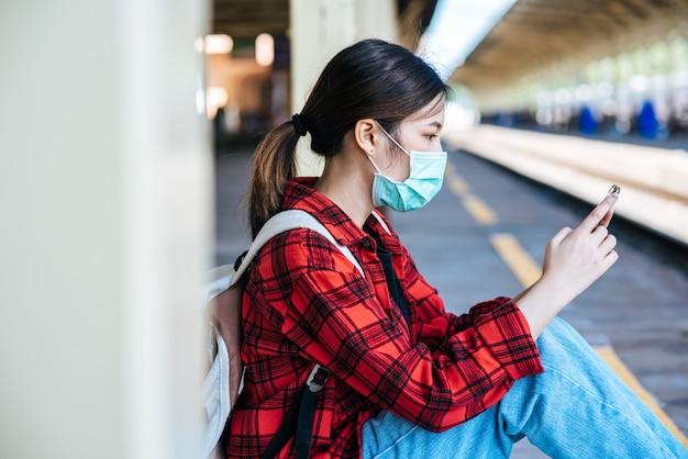 Туристы сидят и смотрят телефоны на пешеходной дорожке у железной дороги. Бесплатные Фотографии