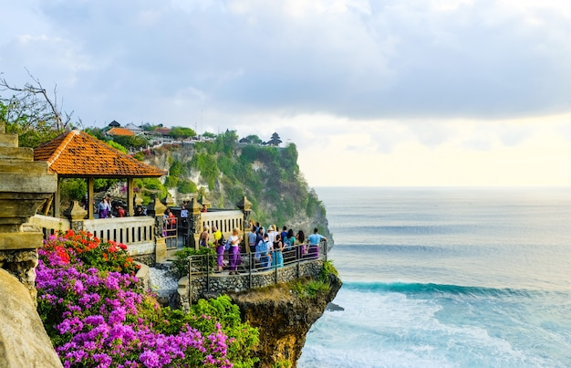 Tourists stand at sunset and admire the scenery on a cliff near the uluwatu temple on the island of bali, indonesia Premium Photo