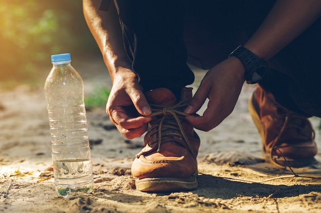 Tourists tied their shoes on a forest path with a water bottle on the side Premium Photo
