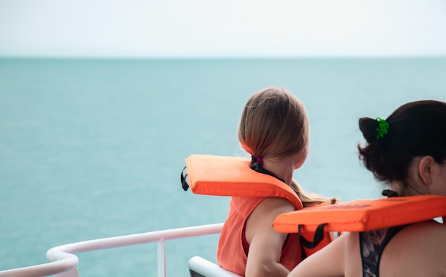 Tourists wear life jackets sitting on the boat. Premium Photo