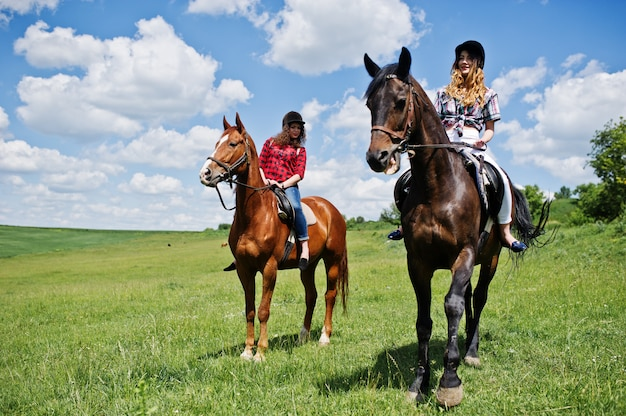 Tow young pretty girls riding a horses on a field at sunny day Premium Photo