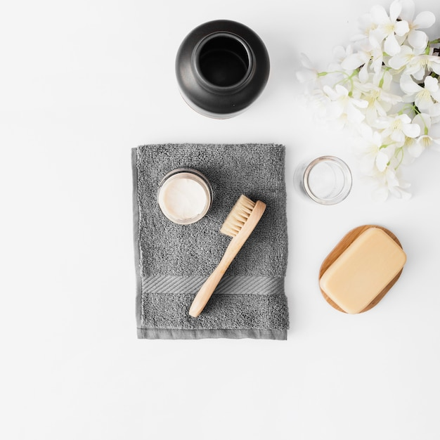 Towel; brush; moisturizing cream; soap; jar and flowers on white surface Free Photo