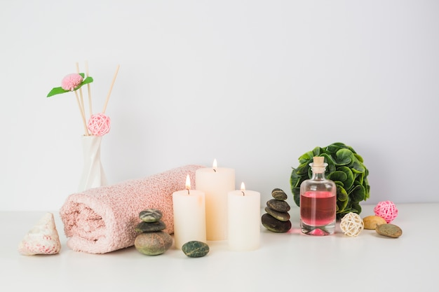 Towel; candles; oil and spa stones on white surface Free Photo