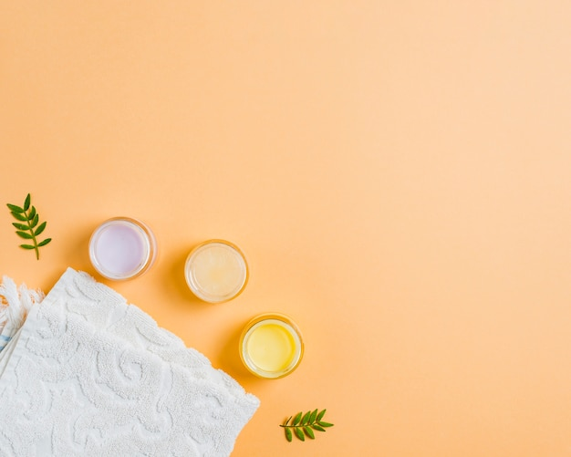 Towel and different moisturizers on colored background Free Photo