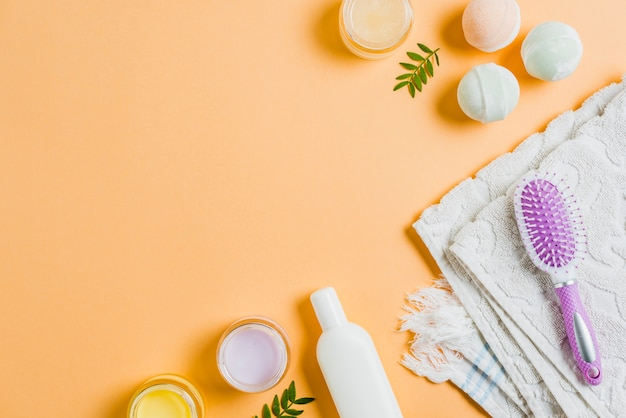 Towel; moisturizers; hairbrush and bath bomb on colored background Free Photo
