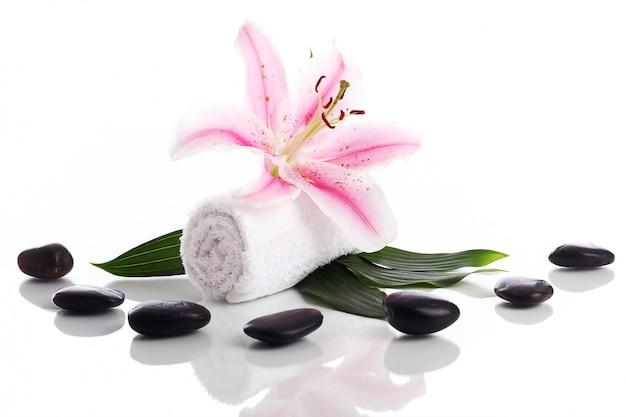 Asciugamano con fiori di giglio e pietre per il massaggio Foto Gratuite