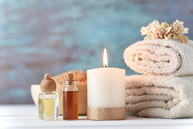 Towels, candle and massage oil on white table Premium Photo