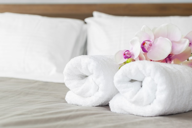 Towels and flower on bed in hotel room Premium Photo