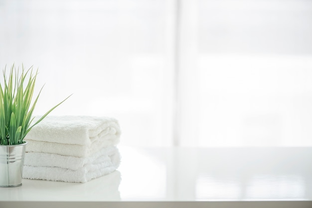 Towels and houseplant on white table with copy space Premium Photo