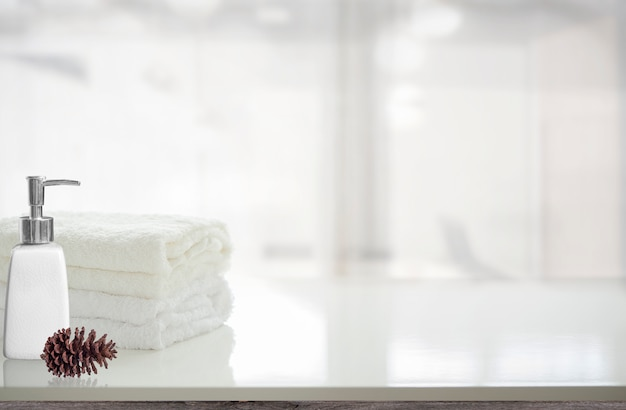 Towels and liquid soap bottle on white table with copy space. Premium Photo