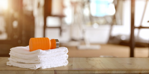 Towels and orange sport bottle with gym Premium Photo