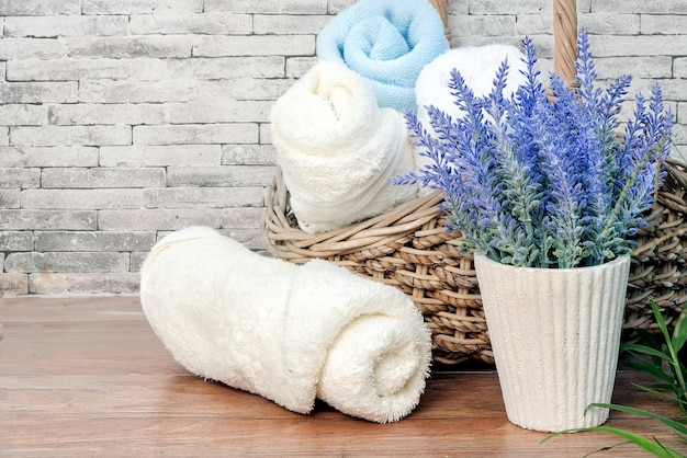 Towels rolls and houseplant on wooden table with old brick wall background. Premium Photo