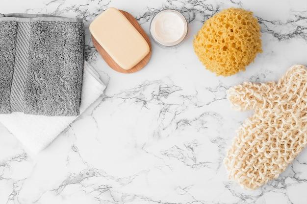 Towels; soap; moisturizing cream; sponge and scrub glove on marble Free Photo