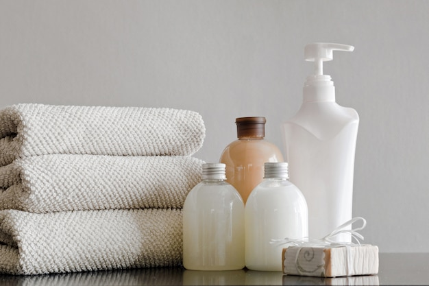 Towels with shampoo, conditioner, shower milk and handmade soap on neutral Premium Photo
