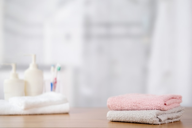 Towels on wooden table with copy space on blurred bathroom. Premium Photo