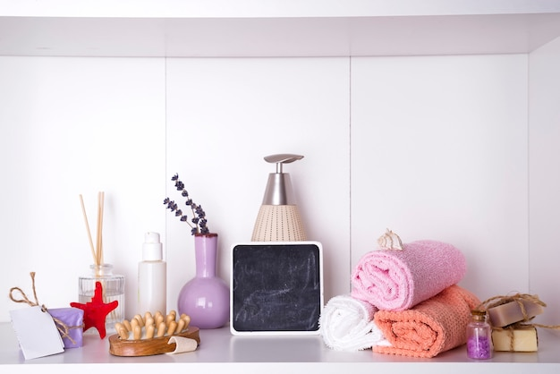 Towels in a wooden tray with aroma chopsticks, candles, massage washcloths and a bottle Premium Photo