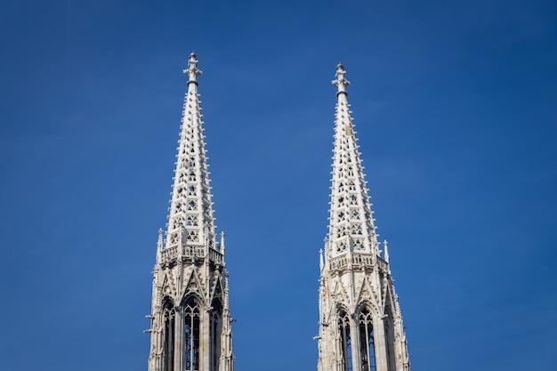 Башни знаменитой церкви вотивкирхе и ясное голубое небо в вене, австрия Premium Фотографии