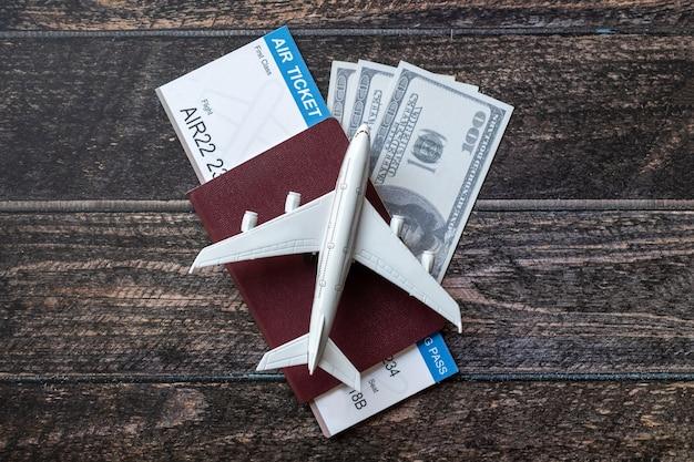 Zabawkowy samolot, bilet lotniczy, karty kredytowe, dolary i paszport na drewnianym stole.  Koncepcja Podróży Zdjęcie Premium