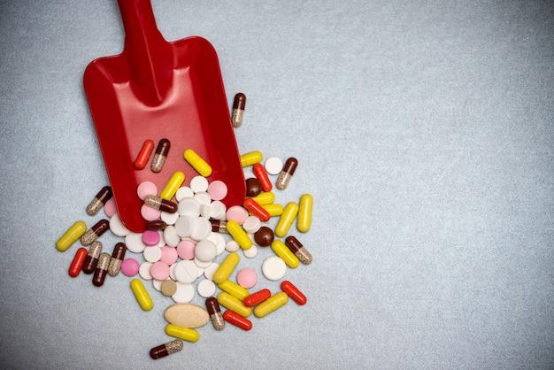 Toy baby scoop full of multi-colored pharmaceutical pills and capsules Premium Photo