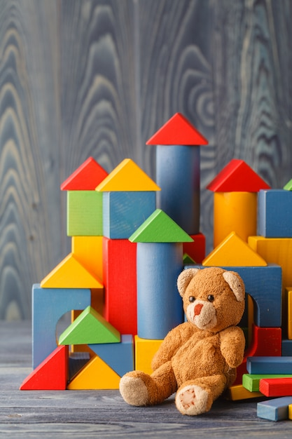 Toy bear and pile wooden building blocks Premium Photo