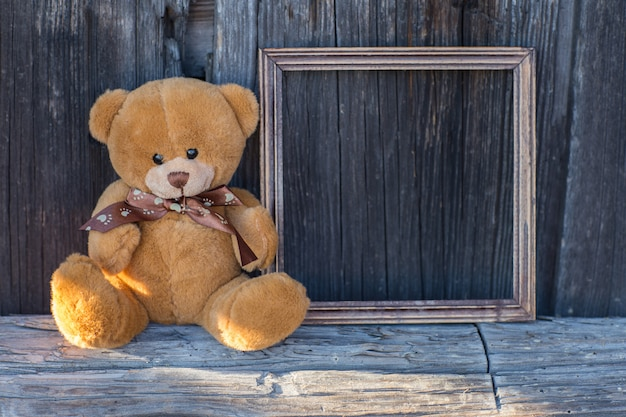Toy bear sits on a table and next to a wooden empty frame Premium Photo