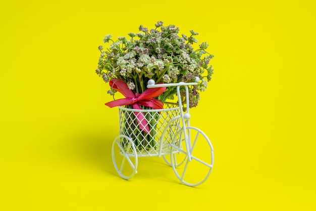 A toy bike carries a flowers. the idea for a postcard. yellow  . minimalism. Premium Photo